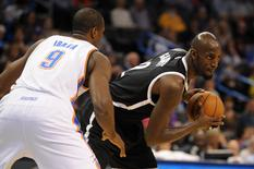 Nov 21, 2014; Oklahoma City, OK, USA; Brooklyn Nets forward Kevin Garnett (2) looks to pass the ball against Oklahoma City Thunder forward Serge Ibaka (9) during the first quarter at Chesapeake Energy Arena. Mandatory Credit: Mark D. Smith-USA TODAY Sports