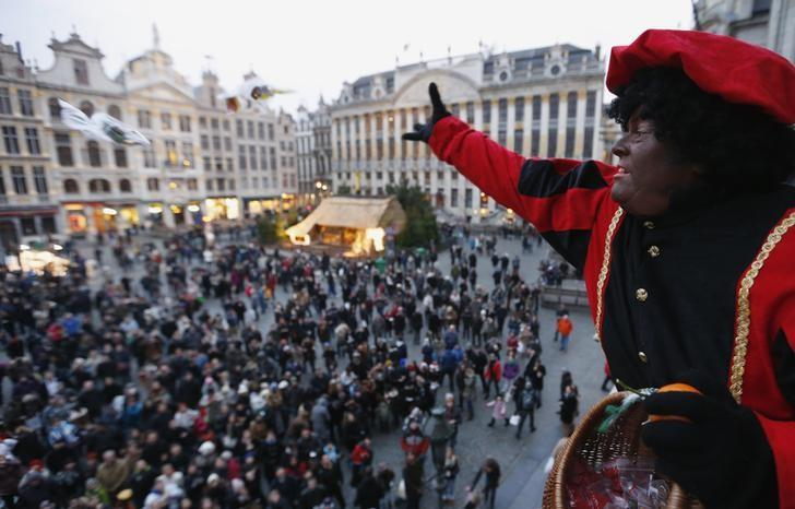 A woman dressed as ''Zwarte Piet'' (Black Pete), the helper of Saint Nicholas, throws candy from the balcony of the City Hall at Brussels' Grand Place December 1, 2012. REUTERS/Francois Lenoir/Files