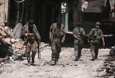 .Бойцы Сирийских демократических сил идут по разрушенным улицам. Сирийские правительственные силы и повстанцы вели ожесточенные бои в Алеппо в пятницу, сообщили источники с обеих сторон, неделю спустя после начала поддерживаемого Россией наступления сирийской армии для получения контроля над городом.  REUTERS/Rodi Said