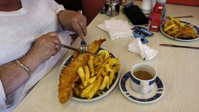 File phot of a woman eating fish and chips at Jack's Fish & Chips in west London May 18, 2012. REUTERS/Eddie Keogh