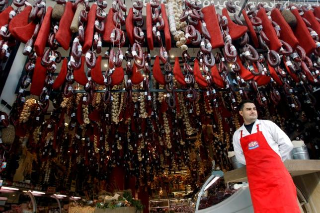 A grocer stands outside his shop in Athens, Greece November 8, 2011.   REUTERS/John Kolesidis/File Photo