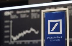 A banners of Deutsche Bank is pictured in front of the German share price index, DAX board, at the stock exchange in Frankfurt, Germany, September 30, 2016. REUTERS/Staff/Remote