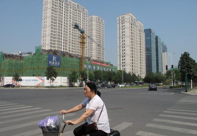 A woman rides past a construction site in Zhengzhou, Henan province, China, September 23, 2016. REUTERS/Yawen Chen