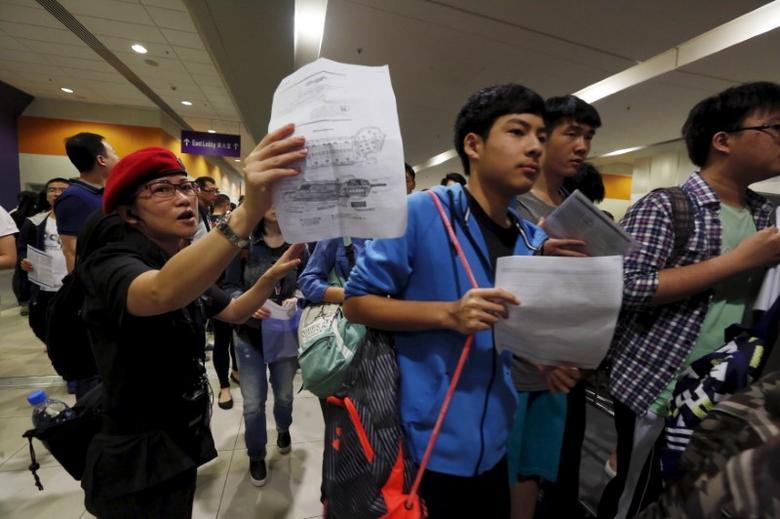 Students enter a hall for SAT examinations beside a security guard at Asia-World Expo near Hong Kong Airport in Hong Kong, China October 3, 2015.  REUTERS/Bobby Yip