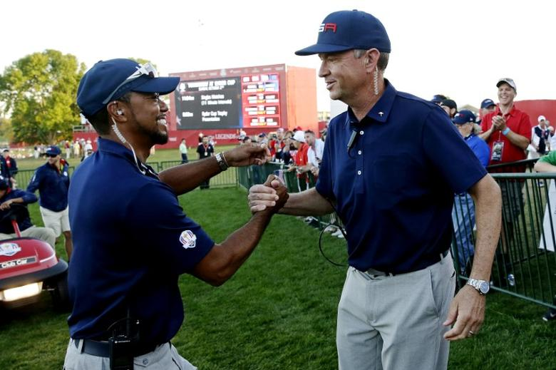 Oct 1, 2016; Chaska, MN, USA; Team USA captain Davis Love III greets Team USA vice-captain Tiger Woods on the 18th hole during the afternoon four-ball matches in the 41st Ryder Cup at Hazeltine National Golf Club. Mandatory Credit: Rob Schumacher-USA TODAY Sports
