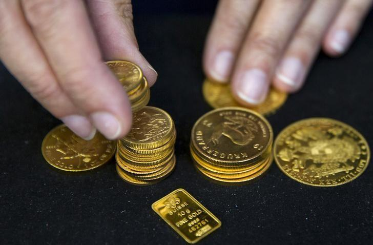 A worker places gold bullion on display at Hatton Garden Metals precious metal dealers in London, Britain July 21, 2015. REUTERS/Neil Hall/Files