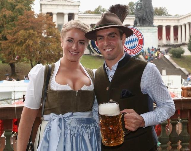 10月2日、ドイツ南部ミュンヘンで、サッカーのドイツ1部ブンデスリーガ、バイエルン・ミュンヘンの選手らが、世界最大のビール祭り「オクトーバーフェスト」に姿を見せた。写真はバイエルン・ミュンヘンのフィリップ・ラーム選手夫妻(2016年 ロイター/Alexandra Beier)