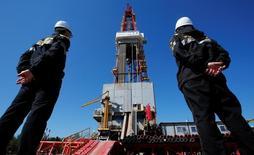 Рабочие смотрят на буровую вышку на нефтяном месторождении Приразломное рядом с Нефтеюганском. Цены на нефть отошли от отметки $50 за баррель в понедельник, несмотря на то, что экспортёры на прошлой неделе договорились ограничить добычу, поскольку трейдеры сомневаются, что этого шага достаточно, чтобы устранить перенасыщение рынка. REUTERS/Sergei Karpukhin/File Photo