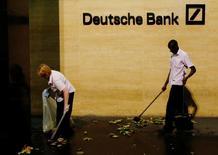 Trabajadores de limpieza limpian el exterior de las oficinas de Deutsche Bank en Londres, 5 de diciembre de 2013. La agencia de calificación Moody's dijo que sería positivo para los tenedores de bonos de Deutsche Bank si el prestamista logra resolver extrajudicialmente las acusaciones en Estados Unidos de irregularidades en las ventas de activos respaldados por hipotecas con un pago de unos 2.750 millones de euros (3.100 millones de dólares). REUTERS/Luke MacGregor/File Photo