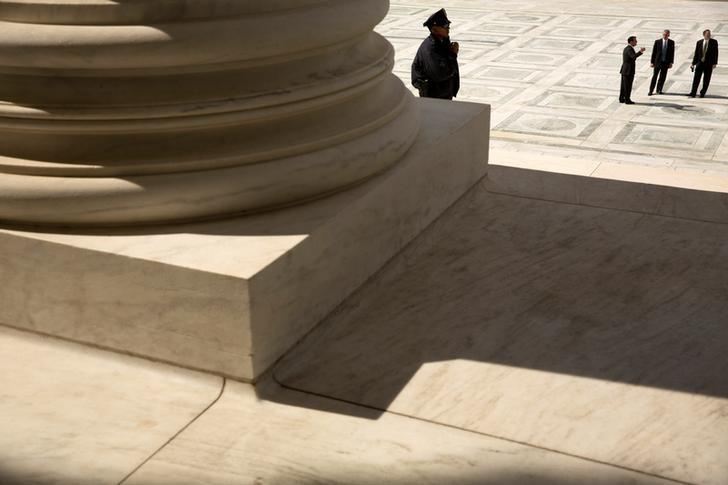 A guard stands on the steps of the U.S. Supreme Court building in Washington, U.S., October 5, 2015.  REUTERS/Jonathan Ernst