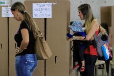 Una mujer con su hija deposita su voto en una urna durante el referendo por la paz entre el Gobierno de Colombia y las FARC, en Medellín, Colombia. 2 de octubre de 2016. La derrota que sufrió el Gobierno de Colombia en un plebiscito para avalar un proceso de paz con la guerrilla de las FARC dificultaría la aprobación de una reforma tributaria, clave para que el país ajuste sus finanzas y mantenga sus calificaciones de riesgo por parte de las agencias internacionales. REUTERS/Fredy Builes