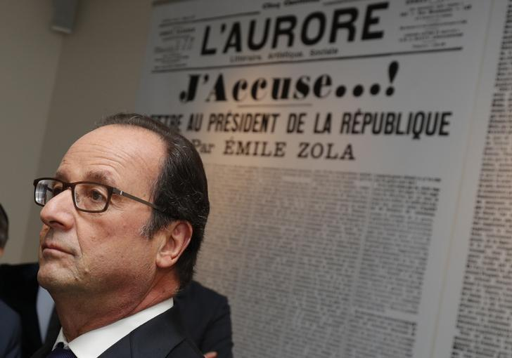 French President Francois Hollande stands in front of a reproduction of French writter Emile Zola's (1840-1902) letter to the President of the Republic ''J'Accuse'' in which he defended Alfred Dreyfus, during a visit to the Zola house and Dreyfus museum in Medan, near Paris, France, October 2, 2016.  REUTERS/Philippe Wojazer