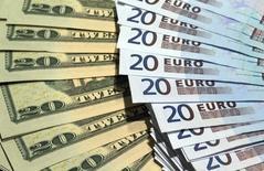 """Банкноты доллара США и евро. Париж, 28 октября 2014 года. Доллар удерживается вблизи двухмесячного максимума к корзине валют в среду благодаря """"ястребиным"""" комментариям представителя Федрезерва США и росту доходности казначейских облигаций. REUTERS/Philippe Wojazer"""