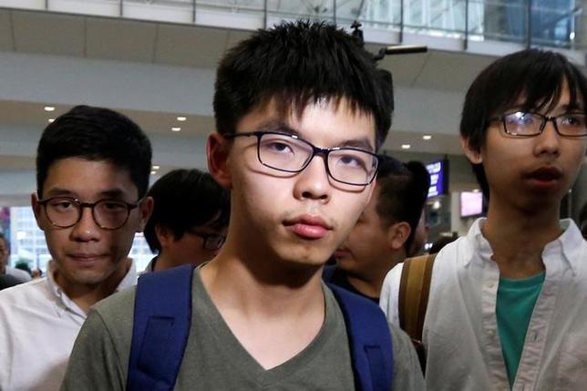 10月5日、タイ当局は、2014年の香港民主化デモを主導した学生運動家、黄之鋒(ジョシュア・ ウォン)氏(写真中央)の入国を拒否した。支援者らは、中国からの圧力によるものだと指摘し、反発を強めている。香港で5日撮影(2016年 ロイター/Bobby Yip)
