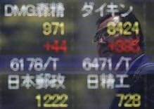 Un hombre se refleja en una pantalla que muestra información bursátil afuera de una correduría en Tokio. 11 de julio de 2016. El índice Nikkei de la bolsa de Tokio subió el miércoles a un máximo de cierre en tres semanas y media gracias a la debilidad del yen. REUTERS/Issei Kato/File Photo