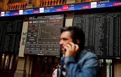 La fortaleza del rebote del sector financiero tras unas jornadas difíciles por los temores sobre Deutsche Bank permitieron al selectivo cerrar con ligeras subidas, tras deambular por zona de pérdidas durante la mayor parte de la sesión. En la imagen de archivo, un hombre habla por teléfono en la Bolsa de Madrid, España, el 24 de junio de 2016.  REUTERS/Andrea Comas