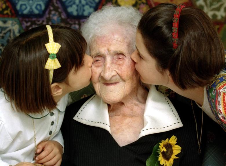 The World's oldest woman, Jeanne Calment, 120 years old, is kissed by two young girls during a special ceremony in a retirement home in Arles, Southern France, February 21, 1995.   REUTERS/Jean-Paul Pelisser/File Photo
