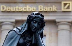 Una estatua junto a un logo del banco alemán Deutsche Bank en Fráncfort, el 26 de enero de 2016. Deutsche Bank estudia escindir su negocio de gestión de activos como una opción para impulsar su capital, publicó el viernes el diario británico Financial Times citando a fuentes cercanas al asunto. REUTERS/Kai Pfaffenbach