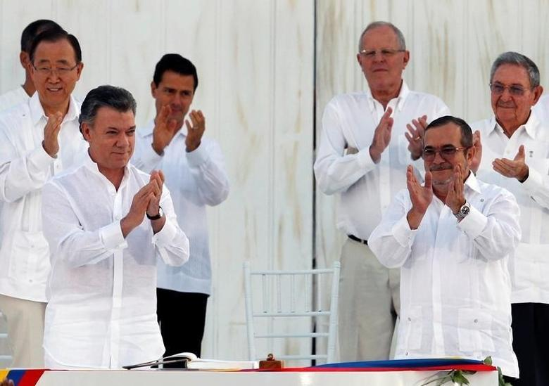 Colombian President Juan Manuel Santos (L) and Marxist rebel leader Rodrigo Londono, better known by the nom de guerre Timochenko, applaud after signing an accord ending a half-century war that killed a quarter of a million people, in Cartagena, Colombia September 26, 2016. REUTERS/John Vizcaino