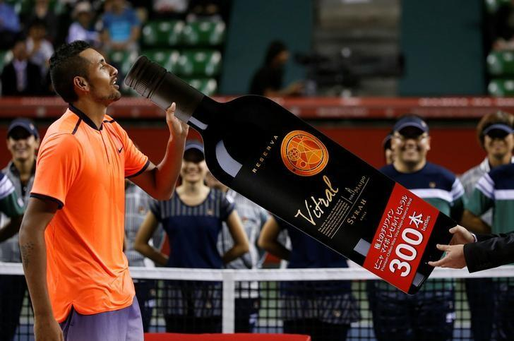 Tennis - Japan Open men's Singles Final Match - Ariake Coliseum, Tokyo, Japan - 09/10/16. Nick Kyrgios of Australia pretends to drink a cutout of a wine bottle which was given to him as an additional prize. REUTERS/Kim Kyung-Hoon