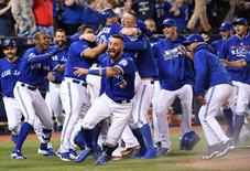 Oct 9, 2016; Toronto, Ontario, CAN; Toronto Blue Jays third baseman Josh Donaldson (20) is congratulated by teammates after scoring the winning run against the Texas Rangers in the 10th inning during game three of the 2016 ALDS playoff baseball series at Rogers Centre. Mandatory Credit: Nick Turchiaro-USA TODAY Sports