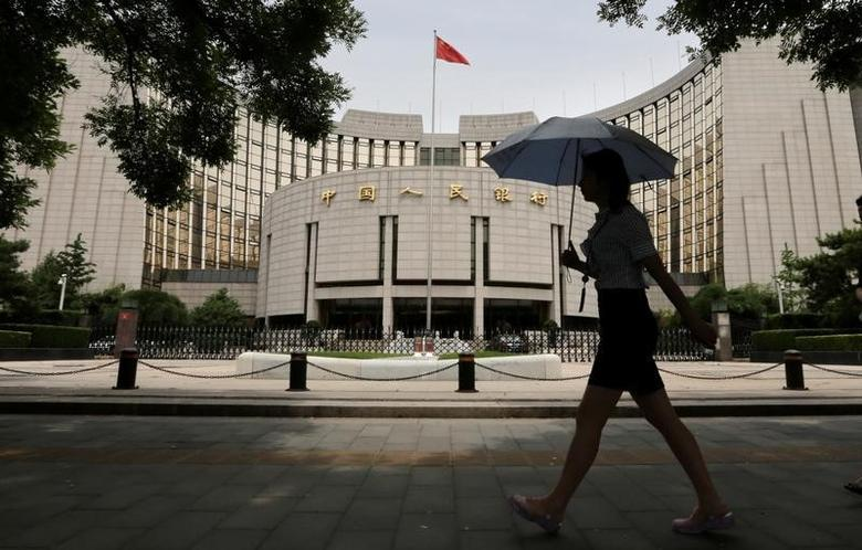 A woman walks past the headquarters of the People's Bank of China (PBOC), the central bank, in Beijing, June 21, 2013.   REUTERS/Jason Lee/File Photo