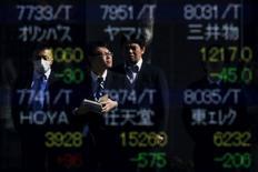 Personas se reflejan en una pantalla electrónica que muestra información bursátil, afuera de una correduría en Tokio, Japón. 10 de febrero de 2016. La mayoría de las bolsas de Asia se debilita el martes, y los precios del petróleo operaban cerca de unos máximos en un año por las expectativas cada vez mayores de que los productores de la OPEP alcancen un acuerdo para recortar su bombeo. REUTERS/Thomas Peter/File Photo
