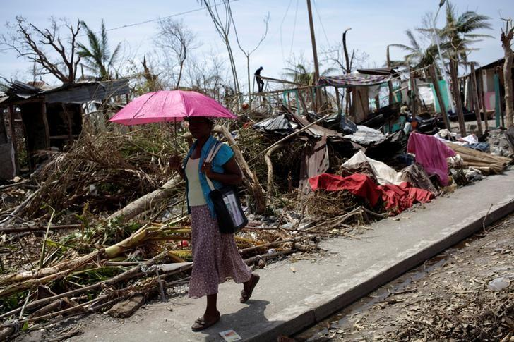 A woman holds an umbrella as she walks next to houses destroyed by Hurricane Matthew in Les Anglais, Haiti, October 10, 2016. REUTERS/Andres Martinez Casares