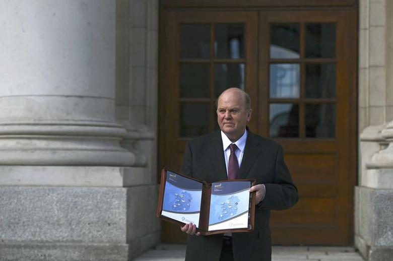 Ireland's Minister for Finance Michael Noonan displays a copy of the budget on the steps of Government Buildings in Dublin, Ireland October 11, 2016.  REUTERS/Clodagh Kilcoyne