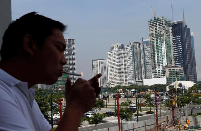 A man lights a cigarette as he takes a break from work at Bonifacio Global City in Taguig, Metro Manila July 4, 2013. REUTERS/Erik De Castro/Files