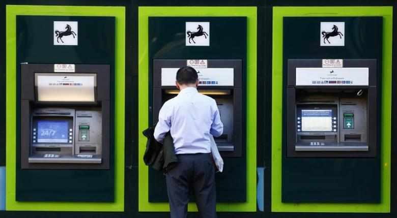 A man uses an ATM  outside a branch of Lloyds Bank in central London October 28, 2014. REUTERS/Andrew Winning