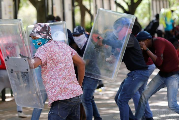 Students demanding free education use shields belonging to private security during a clash with police officers at the Johannesburg's University of the Witwatersrand, South Africa, October 11,2016. REUTERS/Siphiwe Sibeko