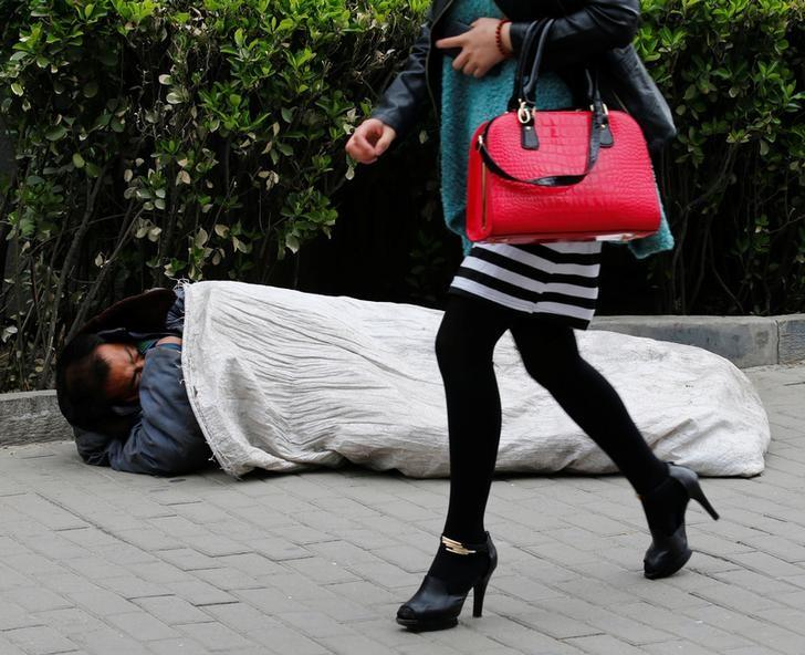 A woman walks past a homeless man sleeping on the street in Beijing April 22, 2013.   REUTERS/Kim Kyung-Hoon/File Photo