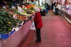 Los precios volvieron a terreno positivo en septiembre, aunque se quedaron ligeramente por debajo de las estimaciones preliminares del INE y de los analistas consultados por Reuters. En esta imagen de archivo, una mujera mira un puesto de frutas y verduras en un mercado de Madrid el 29 de enero de 2013.  REUTERS/Juan Medina/File Photo
