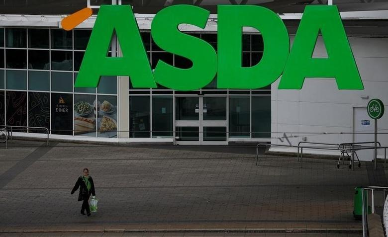 An ASDA employee walks beneath a company logo outside a store in Manchester, northern England, July 8 , 2016. REUTERS/Phil Noble/File Photo