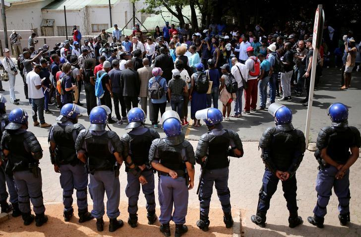Riot police officers keep watch as students chant slogans outside the Hillbrow magistrate court during an appearance of their colleagues who were arrested during a protest demanding free education at the Johannesburg's University of the Witwatersrand, South Africa, October 12, 2016. REUTERS/Siphiwe Sibeko