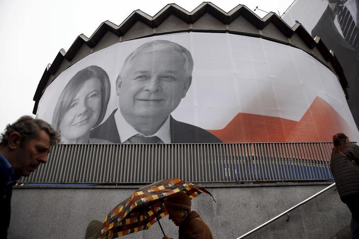 People walk past a giant picture of late Polish president Lech Kaczynski and his wife Maria, who died six years ago when a Polish government plane crashed in Smolensk, Russia, hanging on a building in the centre of Warsaw, Poland April 10, 2016.   REUTERS/Kacper Pempel/Files