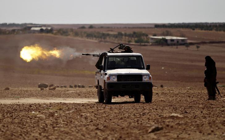 Rebel fighters shoot their weapon towards Dabiq town in northern Aleppo countryside, Syria October 16, 2016. REUTERS/Khalil Ashawi