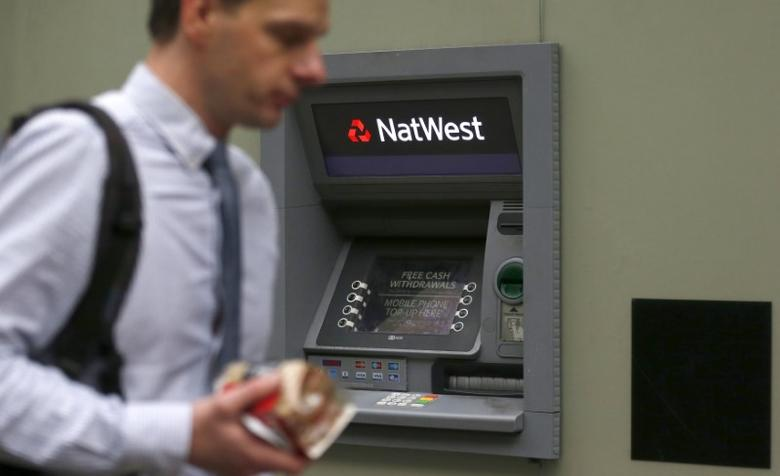 A man walks past a cash machine outside a NatWest bank in London December 3, 2013. REUTERS/Suzanne Plunkett