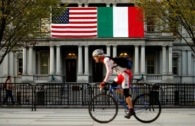 A cyclist passes flags of the U.S. and Italy draped over the Eisenhower Executive Office Building in preparation for Tuesday's state visit by Italian Prime Minister Matteo Renzi, beside the White House in Washington, U.S. October 17, 2016 . REUTERS/Kevin Lamarque