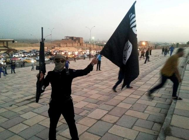 10月12日、イラクにおいてイスラム系過激派組織「イスラム国(IS)」を倒す方法はある。写真はイラク北部のモスルで旗をかざすIS戦闘員。2014年6月撮影(2016年 ロイター)