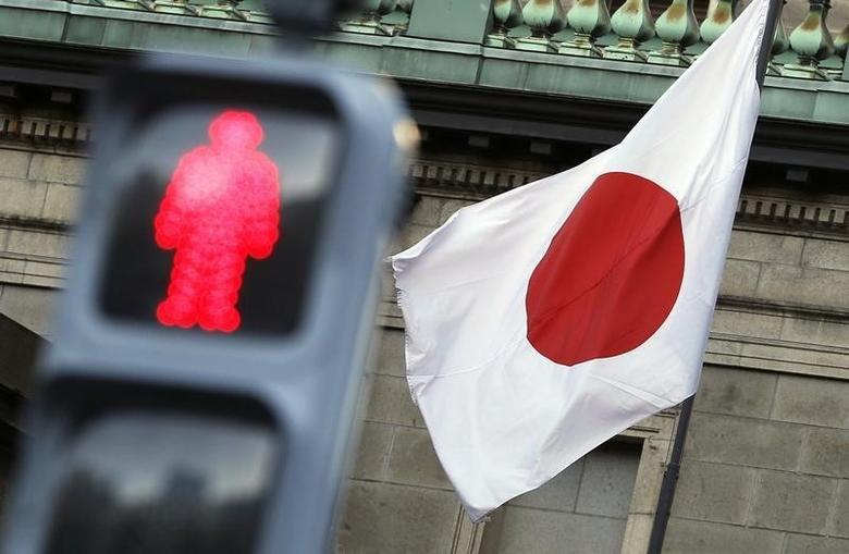 2014年11月19日,日本央行总部大楼前的国旗和交通信号灯。REUTERS/Yuya Shino