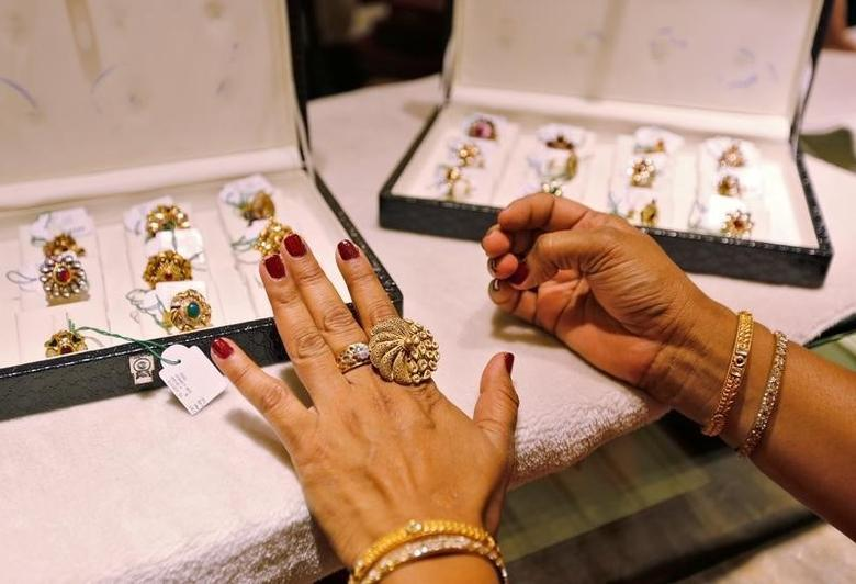 A woman tries on a gold ring inside a jewellery showroom on the occasion of Akshaya Tritiya, a major gold buying festival, in Ahmedabad, May 9, 2016. REUTERS/Amit Dave/Files