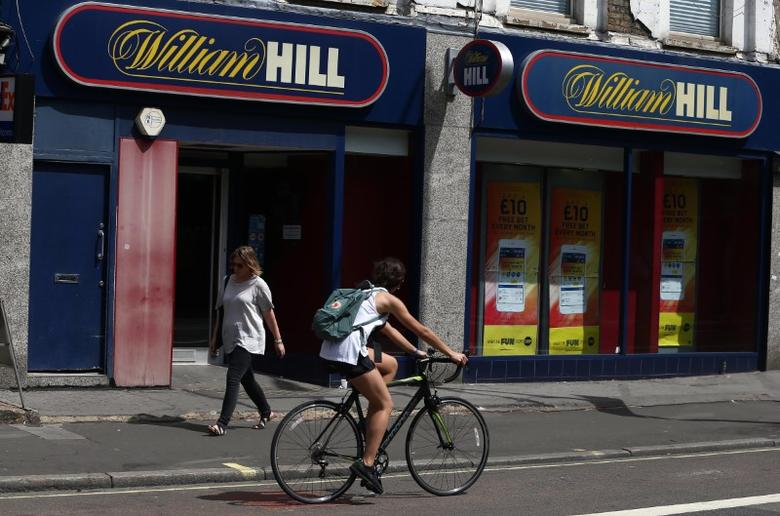 A cyclist passes a William Hill betting shop in London, Britain July 25, 2016. REUTERS/Neil Hall