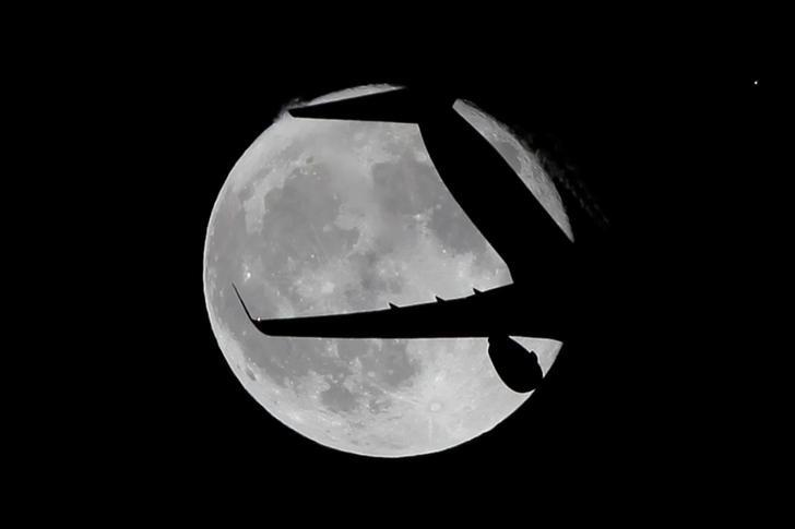 A Ryanair passenger aircraft flies past a super moon in Ardales, southern Spain, October 17, 2016. REUTERS/Jon Nazca