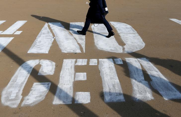 A woman walks on a graffiti reading ''NO CETA'', referring to the Comprehensive Economic and Trade Agreement, in Brussels, Belgium, October 13, 2016.  REUTERS/Francois Lenoir