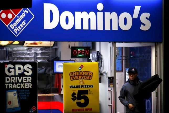 A worker carries a pizza for delivery as he exits a Domino's pizza store in Sydney, Australia, August 12, 2015.   REUTERS/David Gray/File Photo