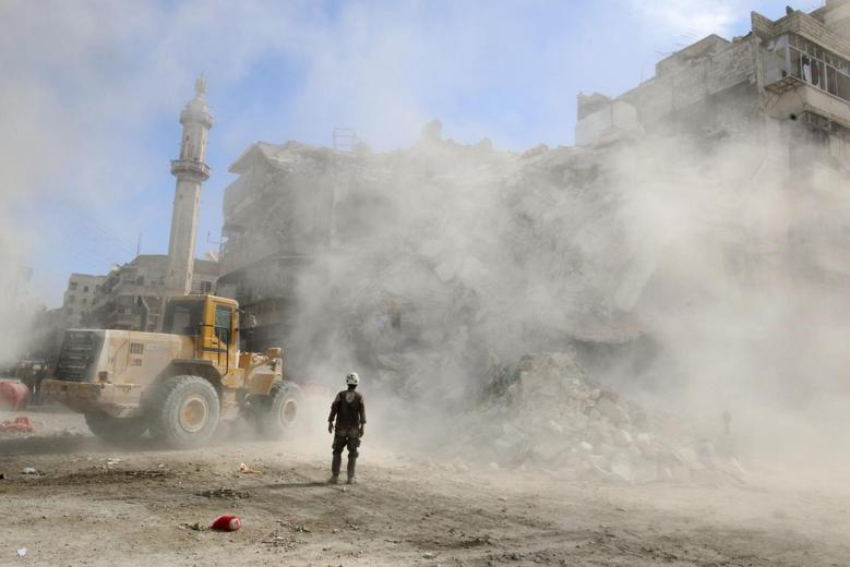 A Civil Defence member stands as a front loader removes debris after an air strike Sunday in the rebel-held besieged al-Qaterji neighbourhood of Aleppo, Syria October 17, 2016. REUTERS/Abdalrhman Ismail