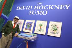 "David Hockney poses with Taschen's ""A Bigger Book"" prior to the opening of the book fair in Frankfurt, Germany October 18, 2016. REUTERS/Kai Pfaffenbach"