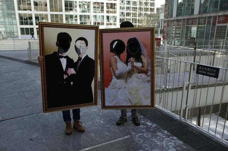 Organizers pose for photographs with two picture boards during a homosexuality promotion campaign on Valentine's Day at a business district in central Beijing February 14, 2011. REUTERS/Petar Kujundzic